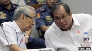 Archbishop Oscar Cruz (left) talks to Rico Puno during a senate inquiry on illegal gambling in Manila on 21 September 2010