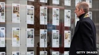 Man looks at adverts in estate agent's window