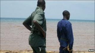 A Burundian policeman (right) and a park ranger (left) look on at a body washed ashore of Lake Tanganika which the River Ruzizi empties into