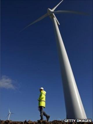 A worker walks past wind turbines