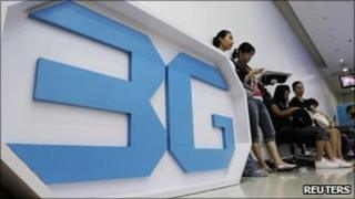 Women stand next to a sign advertising 3G networks in Bangkok