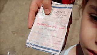 Palestinian refugee holds ration book