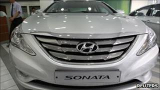 A salesperson walks past a Hyundai Sonata car on display at a Hyundai Motor showroom in Seoul