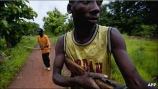 Members of the self-defence group known as the Arrow Boys patrol in a village between the southwestern towns of Yambio and Tambura in southern Sudan on May 22, 2010, against attacks from the Ugandan Lord's Resistance Army (LRA) rebel group