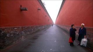 Two women talk in an alleyway in the imperial palace in Beijing