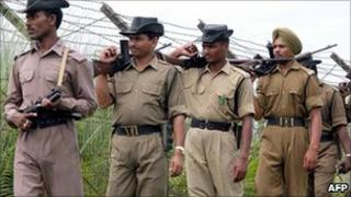 Indian Border Security Force soldiers patrol along the fenced India-Bangladesh International border in Satrasal