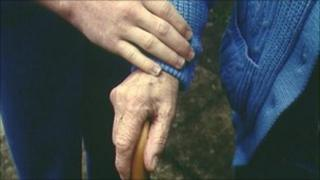 Carer holds elderly person's hand