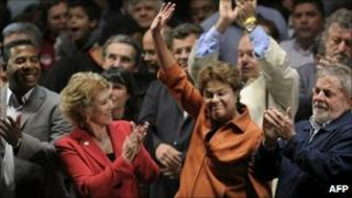 Dilma Rousseff, arms raised, flanked by President Lula (right) and PT congressional candidates Marta Suplicy and Netinho de Paula