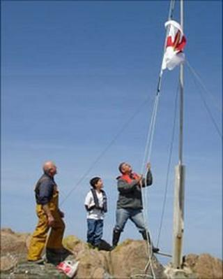 Flag raised on Grosse Rocque in 2009