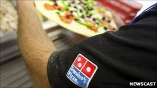 A Domino's employee preparing pizza