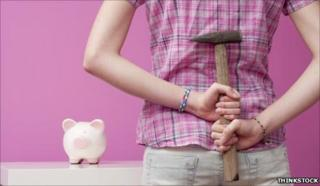 Woman with hammer to break piggy bank