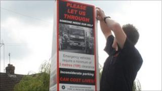 Firefighter putting up poster