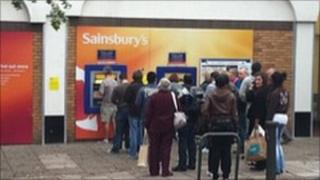 Customers at cashpoint outside Sainsbury's store in New Barnet, north London Photo: AraTheCoach on Twitter