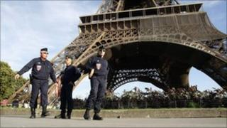 French police officers patrol under the Eiffel Tower in Paris