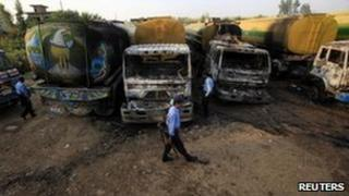 Pakistani police survey the site where fuel tankers were attacked near Islamabad, 4 October