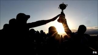 The Ryder Cup is hoistedby the winning Europe team.