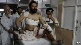A man injured in the blasts is brought to Kandahar's hospital
