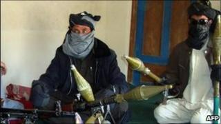 Taliban fighters display their weapons