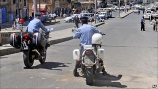 Yemeni policemen attend the scene where an attack took place on a convoy carrying a senior British diplomat in Sanaa