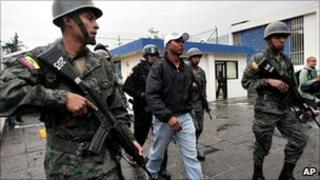 Soldiers escort a police officer arrested in connection with the revolt against President Correa