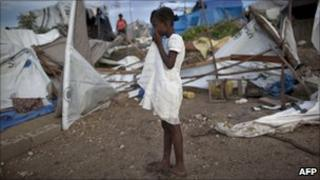 A girl stands next to tents destroyed by heavy rains in Port-au-Prince on 25 September