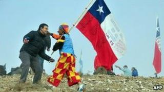 A man in a clown suit holding a Chilean flag celebrates with a TV reporter after one of the drills working to rescue the 33 trapped miners finally reached their shelter in the San Jose mine, near Copiapo, Chile