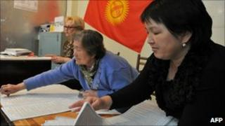 Kyrgyz women prepare forms at a polling station in Osh on 9 October 2010