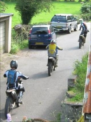 Off-road motorbikes being ridden in a lane