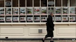 Woman walks past estate agent's window