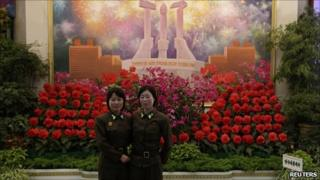 North Korean female soldiers pose for photographs in front of a display of 'kimjongilia' and 'kimilsungia' flowers