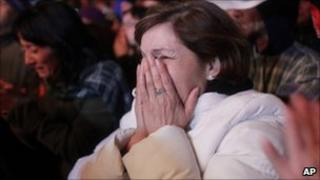 A woman reacts as she watches the televised rescue