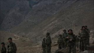 Afghan soldiers stand guard near the site of a plane crash, on the mountain side above them, east of Kabul, Afghanistan, Wednesday Oct. 13, 2010.