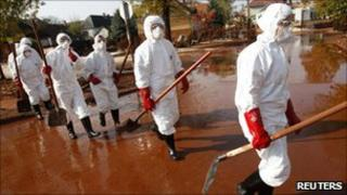 Volunteers in protective clothing walking through red mud in the flooded village of Devecser, Hungary