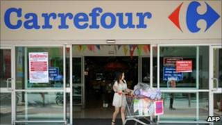 A Thai shopper leaving a French retail giant Carrefour supermarket in Bangkok