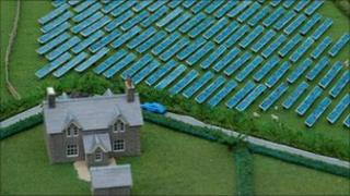 Model of a farm house with solar panels in adjacent field
