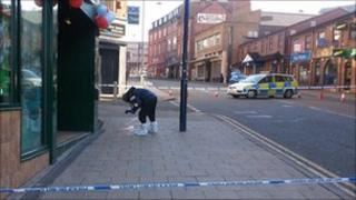 A forensics officer photographs evidence from the stabbing scene in Hanley