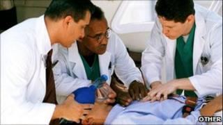 Three doctors treat a man on stretcher