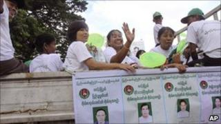 Members of the Union Solidarity and Development Party (USDP) wave from a campaign vehicle on 13 October 2010