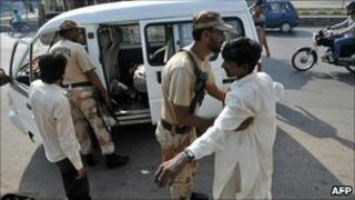 A Pakistani paramilitary soldier frisks a man in Karachi