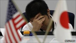 A foreign exchange dealer reacts at a trading room in Tokyo