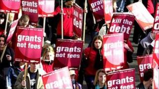 Students holding signs reading grants not fees