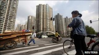 A woman pushes her bikes past a residential development in Shanghai