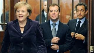 Angela Merkel, Dmitry Medvedev and Nicolas Sarkozy arrive for a meeting at their summit in Deauville, 19 October