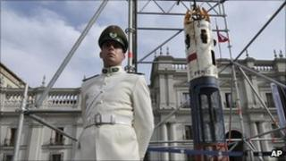 A police officer stands guard by the capsule outside the presidential palace in Santiago