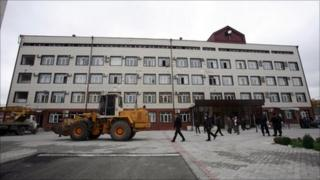 Vehicles stand outside a building inside the Chechen parliamentary compound after the attack, 19 October