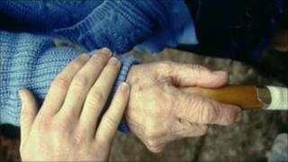 Elderly patient and carer hold hands