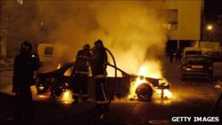 Firefighters try to extinguish a car after rioting in Clichy-sous-Bois (30 October 2005)