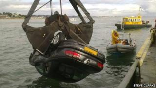 A crane lifting the car from the sea