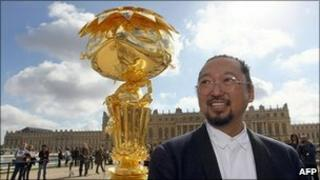 Takashi Murakami in front of Oval Buddha Gold in the Versailles courtyard