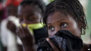 Women cover their mouths as their children are treated in hospital in Grande-Saline, Haiti, 23 October 2010